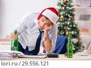 Купить «Young handsome employee celebrating Christmas at workplace», фото № 29556121, снято 30 июля 2018 г. (c) Elnur / Фотобанк Лори