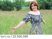 Купить «Beautiful smiling middle-aged woman in nature in summer», фото № 29560949, снято 19 июня 2017 г. (c) Володина Ольга / Фотобанк Лори