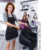 Купить «Hairdresser inviting to sit in chair», фото № 29561237, снято 26 июня 2018 г. (c) Яков Филимонов / Фотобанк Лори