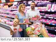 Купить «parents with daughter choosing meat in refrigerated section in hypermarket», фото № 29561381, снято 23 января 2019 г. (c) Яков Филимонов / Фотобанк Лори