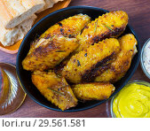 Купить «Crispy roasted chicken wings in black bowl», фото № 29561581, снято 22 ноября 2019 г. (c) Яков Филимонов / Фотобанк Лори