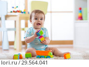 Купить «baby playing toys in nursery or daycare», фото № 29564041, снято 14 декабря 2018 г. (c) Оксана Кузьмина / Фотобанк Лори
