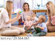 Купить «Mentor and 1 years old babies play with educational toys in kindergarten or daycare centre», фото № 29564061, снято 14 декабря 2018 г. (c) Оксана Кузьмина / Фотобанк Лори