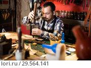 Купить «Professional man processing leather», фото № 29564141, снято 19 января 2019 г. (c) Яков Филимонов / Фотобанк Лори