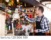 Купить «Worker choosing thread for sewing», фото № 29564189, снято 19 января 2019 г. (c) Яков Филимонов / Фотобанк Лори
