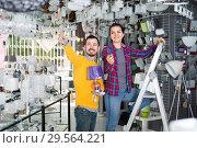 Купить «Man and girl looking at an assortment of chandeliers», фото № 29564221, снято 16 февраля 2017 г. (c) Яков Филимонов / Фотобанк Лори