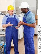 Купить «Construction workers discussing upcoming repairs», фото № 29564437, снято 4 мая 2018 г. (c) Яков Филимонов / Фотобанк Лори