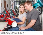Купить «Couple is shopping and choosing new motobike», фото № 29564477, снято 8 мая 2018 г. (c) Яков Филимонов / Фотобанк Лори