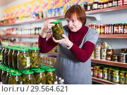 Купить «female customer choosing canned jar of cucumbers», фото № 29564621, снято 15 декабря 2017 г. (c) Яков Филимонов / Фотобанк Лори