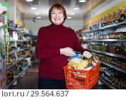 Купить «Smiling female customer with shopping basket standing», фото № 29564637, снято 15 декабря 2017 г. (c) Яков Филимонов / Фотобанк Лори