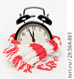 Купить «The black alarm clock is wrapped in a warm knitted red and white scarf. Time, about twelve.», фото № 29564861, снято 13 декабря 2018 г. (c) Элина Гаревская / Фотобанк Лори