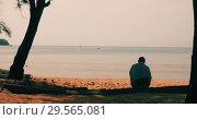 Купить «Anonymous man sitting on sandy beach», видеоролик № 29565081, снято 3 декабря 2018 г. (c) Ekaterina Demidova / Фотобанк Лори
