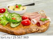 Купить «Pieces of Italian prosciutto on a wooden cutting board», фото № 29567969, снято 12 декабря 2018 г. (c) Татьяна Ляпи / Фотобанк Лори