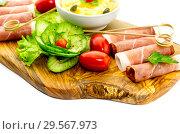 Купить «Pieces of Italian prosciutto on a wooden cutting board», фото № 29567973, снято 12 декабря 2018 г. (c) Татьяна Ляпи / Фотобанк Лори