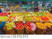 Russia, Samara, November 2018: buyers choose a variety of fruits in a large supermarket. Text in Russian: apples, pear, lemon, persimmon, bananas, Turkey, China. Редакционное фото, фотограф Акиньшин Владимир / Фотобанк Лори