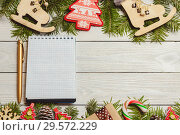 White wooden christmas background with fir branches, cones, decor, notebook, top view, copyspace. Стоковое фото, фотограф Максим Бейков / Фотобанк Лори