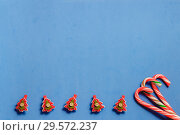 Top view three candy canes and five red fir tree shaptd pins on blue background. Стоковое фото, фотограф Максим Бейков / Фотобанк Лори