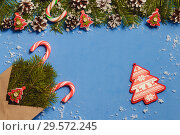 Top view candy canes and red fir tree shaped pins in brown craft envelope on blue background. Стоковое фото, фотограф Максим Бейков / Фотобанк Лори