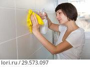Купить «Woman with detergent cleaning tiled wall», фото № 29573097, снято 22 ноября 2018 г. (c) Яков Филимонов / Фотобанк Лори
