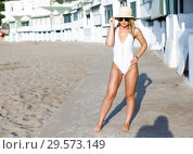 Купить «Young woman in swimsuit with hat posing near hotel wall at sea shore», фото № 29573149, снято 10 июля 2018 г. (c) Яков Филимонов / Фотобанк Лори