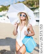 Купить «Young female in swimsuit with umbrella and bag walking at beach», фото № 29573153, снято 10 июля 2018 г. (c) Яков Филимонов / Фотобанк Лори