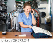 Smiling girl worker of laundry talking on phone while checking clothes taken for dry cleaning. Стоковое фото, фотограф Яков Филимонов / Фотобанк Лори