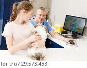 Купить «Smiling girl with puppy visiting veterinarian clinic», фото № 29573453, снято 3 мая 2018 г. (c) Яков Филимонов / Фотобанк Лори