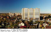 High-rise residential building under construction among private houses in Russia. Стоковое видео, видеограф Володина Ольга / Фотобанк Лори
