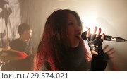 Купить «The singer performs a song with his rock band at the club», видеоролик № 29574021, снято 16 января 2019 г. (c) Константин Шишкин / Фотобанк Лори
