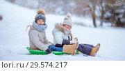 Купить «Adorable little happy girls sledding in winter snowy day.», фото № 29574217, снято 8 января 2016 г. (c) Дмитрий Травников / Фотобанк Лори