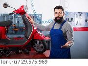 Купить «Man worker demonstrating motorbikes and scooters», фото № 29575969, снято 19 января 2019 г. (c) Яков Филимонов / Фотобанк Лори
