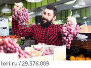 Купить «Cheerful male seller offering grapes in shop», фото № 29576009, снято 15 ноября 2016 г. (c) Яков Филимонов / Фотобанк Лори