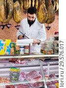 Young male seller offering displayed sorts of meat. Стоковое фото, фотограф Яков Филимонов / Фотобанк Лори