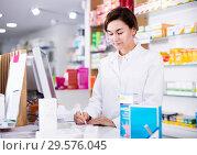 Купить «Pharmacist ready to assist in choosing at counter», фото № 29576045, снято 31 января 2017 г. (c) Яков Филимонов / Фотобанк Лори