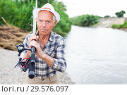 Купить «Mature fisherman with rod at riverside», фото № 29576097, снято 10 июня 2018 г. (c) Яков Филимонов / Фотобанк Лори