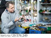 Купить «Senior male is choosing old artifact at the antique market», фото № 29576249, снято 23 октября 2017 г. (c) Яков Филимонов / Фотобанк Лори