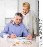 attentive mature couple at table attentively study documents. Стоковое фото, фотограф Яков Филимонов / Фотобанк Лори