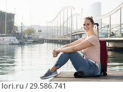 Купить «Positive female tourist standing at pier in cold spring day», фото № 29586741, снято 4 мая 2017 г. (c) Яков Филимонов / Фотобанк Лори