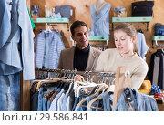 Купить «Smiling woman and man are choosing variety clothes on hanger», фото № 29586841, снято 12 марта 2018 г. (c) Яков Филимонов / Фотобанк Лори
