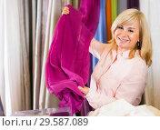 Купить «Mature woman customer choosing color curtains», фото № 29587089, снято 17 января 2018 г. (c) Яков Филимонов / Фотобанк Лори
