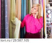 Купить «woman choosing curtains and using phone», фото № 29587105, снято 17 января 2018 г. (c) Яков Филимонов / Фотобанк Лори