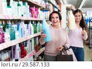 Купить «woman picking bottles with shampoo and conditioner from shelf in cosmetics store», фото № 29587133, снято 20 января 2019 г. (c) Яков Филимонов / Фотобанк Лори