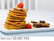 Купить «Pancakes served with fruit, honey, chocolate and whipped cream», фото № 29587193, снято 16 сентября 2019 г. (c) Яков Филимонов / Фотобанк Лори