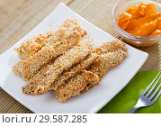 Купить «Fried chicken fingers from fillet in sesame served at plate on table», фото № 29587285, снято 16 января 2019 г. (c) Яков Филимонов / Фотобанк Лори