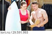 Купить «Girl discussing surf rental with man», фото № 29591993, снято 30 апреля 2018 г. (c) Яков Филимонов / Фотобанк Лори