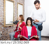 Купить «Positive young man hairdresser cuts hair of young woman with magazine at salon», фото № 29592069, снято 25 апреля 2018 г. (c) Яков Филимонов / Фотобанк Лори