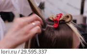 Купить «Professional Hairdresser making a hairdo to a fair-haired model», видеоролик № 29595337, снято 8 октября 2018 г. (c) Pavel Biryukov / Фотобанк Лори
