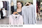 Купить «Shop assistant demonstrating jacket on hanger», фото № 29596009, снято 10 октября 2018 г. (c) Яков Филимонов / Фотобанк Лори