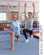Купить «Happy woman and man acrobats training gymnastic action at gym», фото № 29596077, снято 18 июля 2018 г. (c) Яков Филимонов / Фотобанк Лори