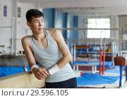 Купить «Positive young man asian acrobat posing at modern sport gym», фото № 29596105, снято 18 июля 2018 г. (c) Яков Филимонов / Фотобанк Лори